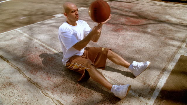 MS Man sitting on basketball court and spinning basket ball on pen/ Man feigning exhaustion, sticking pen in shoelaces with ball still spinning on it and lying down/ Harlem, New York
