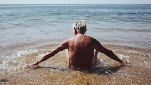 stockvideo's en b-roll-footage met ms man sitting on beach, splashing water / corsept, loire-atlantique, france - alleen één seniore man