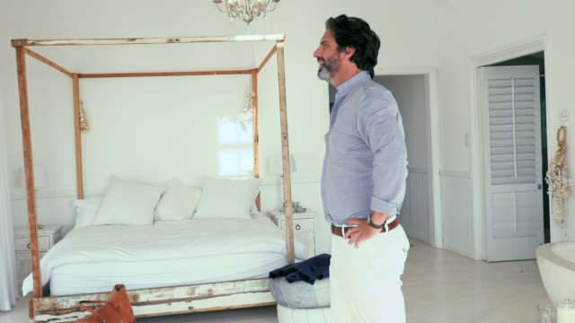 vídeos de stock e filmes b-roll de man sitting on bed - remover