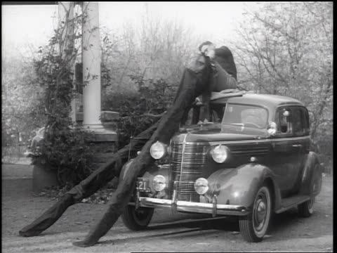 stockvideo's en b-roll-footage met b/w 1938 man sitting on car roof putting on long stilts - 1938