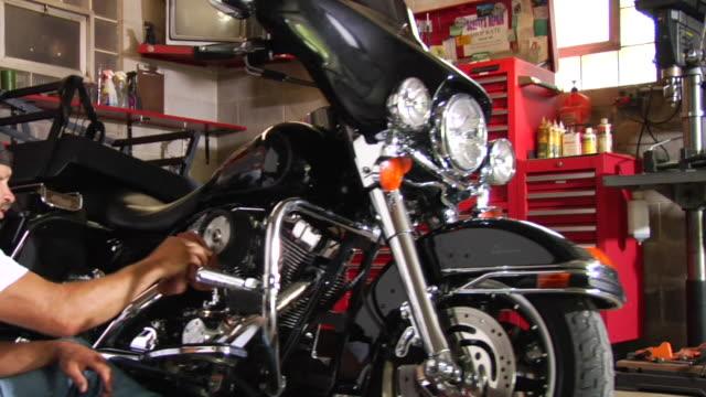 ms pan man sitting on floor of garage while working on motorcycle/ appleton, wisconsin - goatee stock videos & royalty-free footage