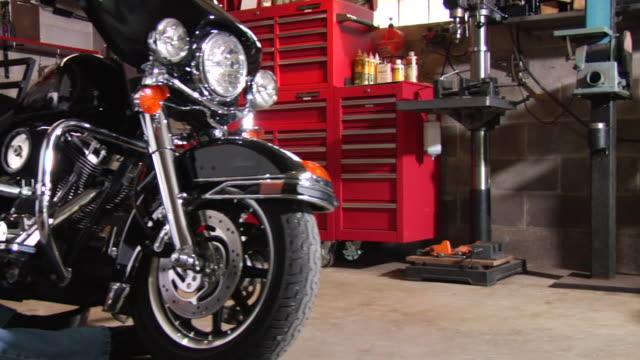 vídeos y material grabado en eventos de stock de ms pan man sitting on floor of garage while working on motorcycle/ appleton, wisconsin - perilla