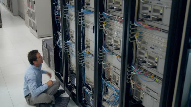 ms man sitting on floor working on server with laptop, sydney, australia - dreiviertelansicht stock-videos und b-roll-filmmaterial