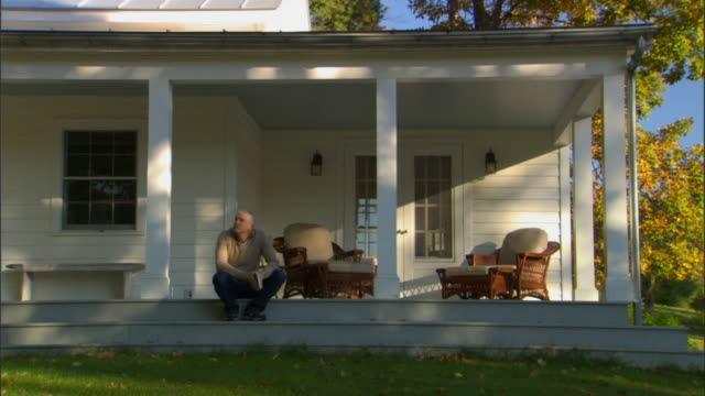 WS Man sitting on front porch steps/ Livingston, New York