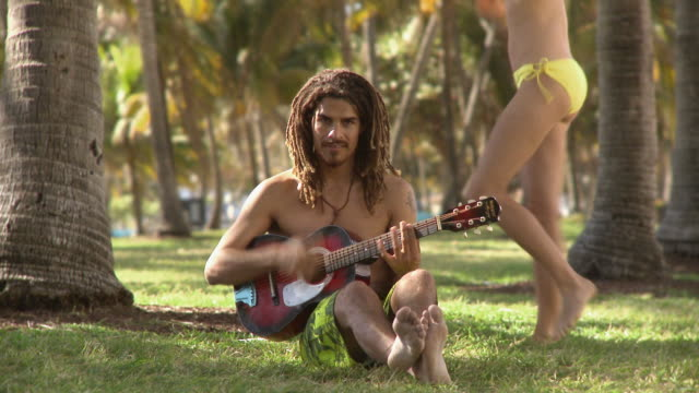 stockvideo's en b-roll-footage met ws man sitting on grass playing guitar and woman dancing in background / south beach, florida, usa - ontbloot bovenlichaam