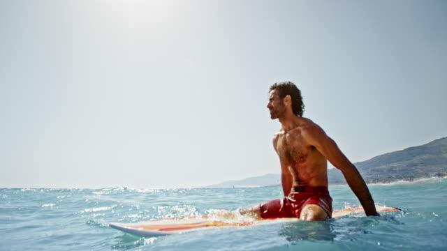 vídeos y material grabado en eventos de stock de slo mo hombre sentado en su tabla de surf en el mar en un día soleado - sentado