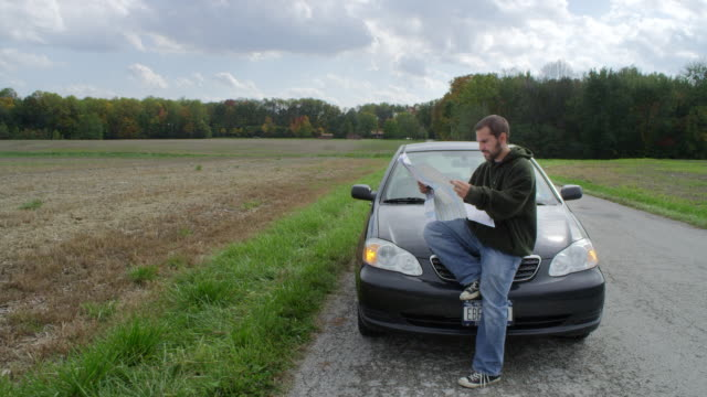 ms man sitting on hood of parked car at rural road and reading road map / illinois, united states - road map stock videos & royalty-free footage