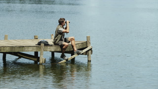 ws of man sitting on jetty with binoculars - osservare gli uccelli video stock e b–roll