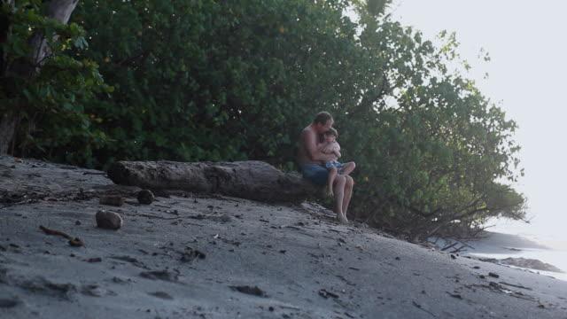 vídeos de stock, filmes e b-roll de ms man sitting on log with boy on his lap on beach / montezuma, puntarenas, costa rica - kelly mason videos