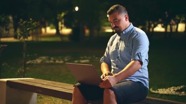 Man sitting on park bench using laptop outdoors at night