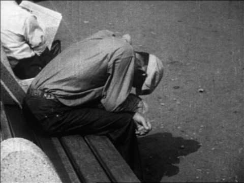 vidéos et rushes de b/w 1929 man sitting on park bench with head down / great depression / newsreel - tous types de crises