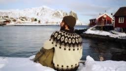 Man sitting on pier in Reine in winter
