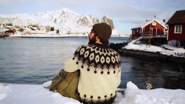 man sitting on pier in reine in winter - jumper stock videos & royalty-free footage