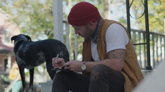 slo mo man sitting on porch at home writes in journal, gives dog a pat - diary stock videos & royalty-free footage