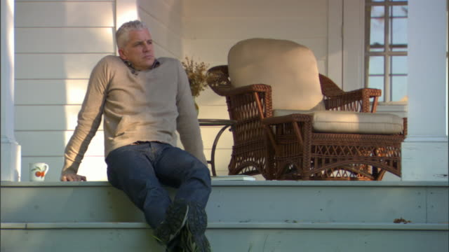 ms td man sitting on porch, drinking coffee and reading book/ livingston, new york - porch stock videos and b-roll footage