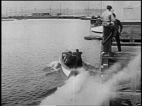 b/w 1916 man sitting on post pulled from dock into harbor by speedboat - 1916 stock videos & royalty-free footage