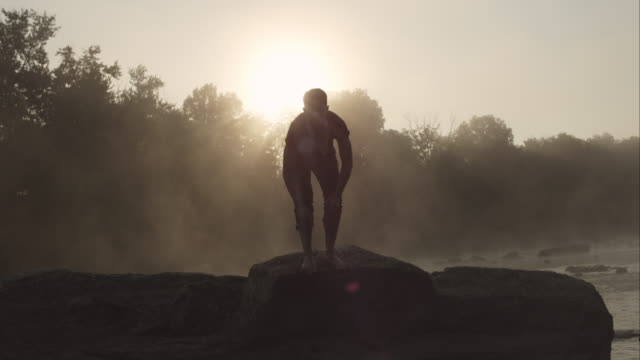 Man sitting on rock looking at camera then standing at sunrise