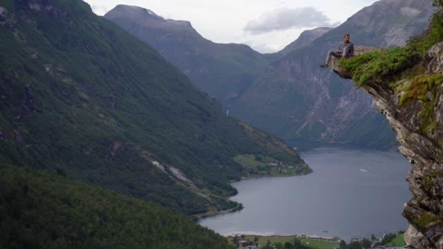 stockvideo's en b-roll-footage met de zitting van de mens op rots dichtbij geirangerfjord in noorwegen - klif