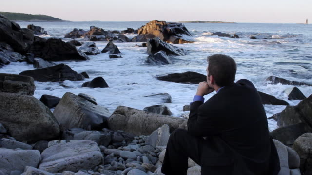 ms man sitting on rocks looking out over ocean / portland, me, united states - horizon stock videos & royalty-free footage
