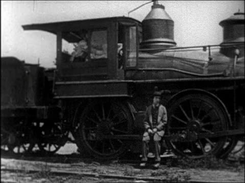 b/w 1927 man sitting on side of train moving slowly on track / 1860s / feature - buster keaton stock videos and b-roll footage