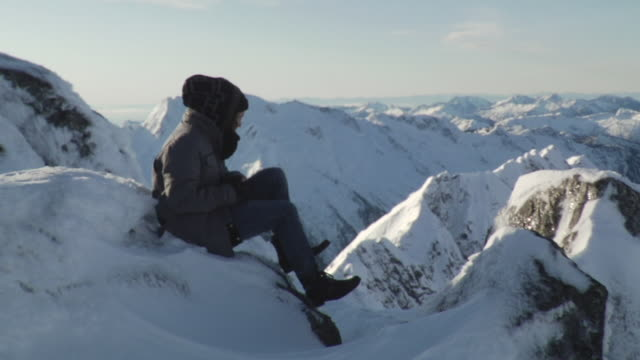 ws zi zo man sitting on snow mountain / vancouver, british colombia, canada - solo uomini giovani video stock e b–roll