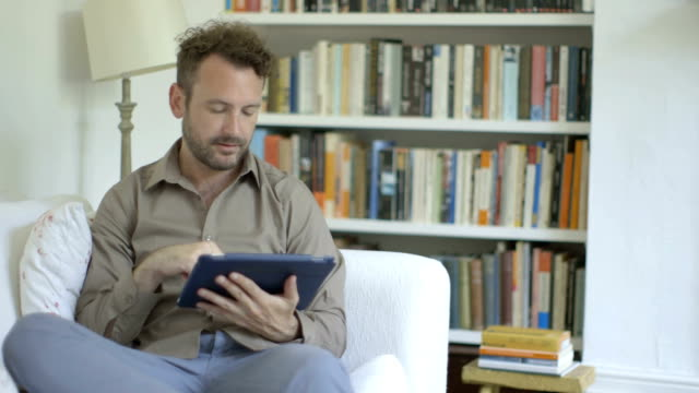 Man sitting on sofa and using digital tablet.