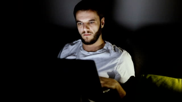 Man sitting on sofa and working on laptop