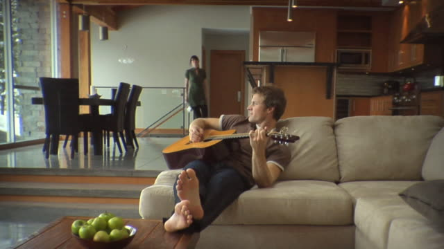 SLO MO WS Man sitting on sofa playing guitar, woman holding newspaper walking upstairs hitting man and smiling / Whistler, British Columbia, Canada