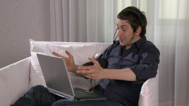 MS Man sitting on sofa, talking into telephone headset and using laptop/ Berlin, Germany