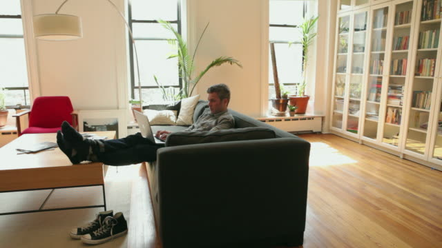 ws man sitting on sofa using laptop / brooklyn, new york city, usa - feet up stock videos and b-roll footage