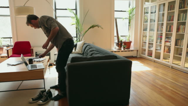 WS Man sitting on sofa using laptop / Brooklyn, New York City, USA