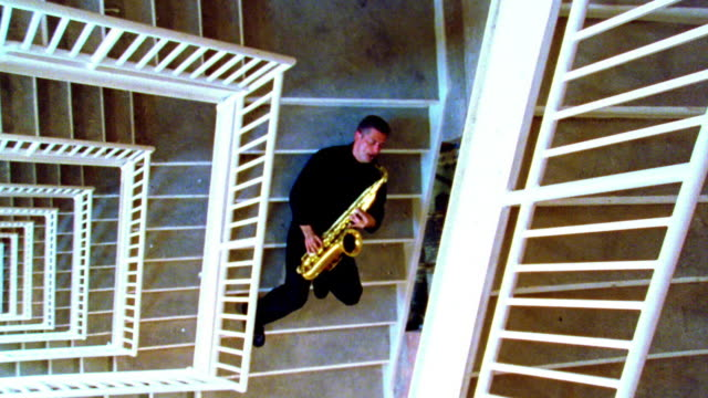 stockvideo's en b-roll-footage met overhead man sitting on stairs playing saxophone - saxofonist