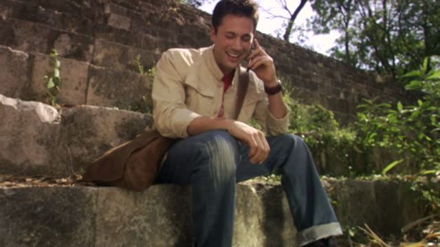 la pan ms man sitting on steps at mayan ruins and talking on cell phone / merida, mexico  - remote location phone stock videos & royalty-free footage