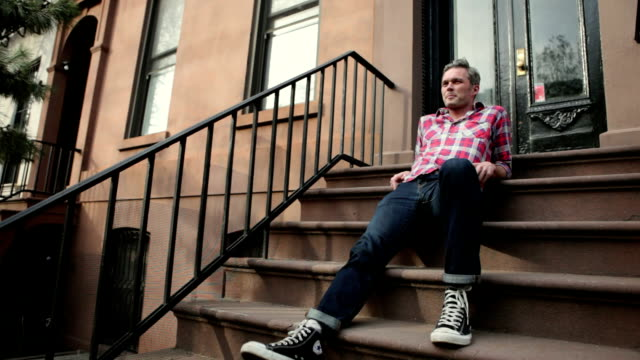 WS Man sitting on stoop of apartment building / Brooklyn, New York City, USA