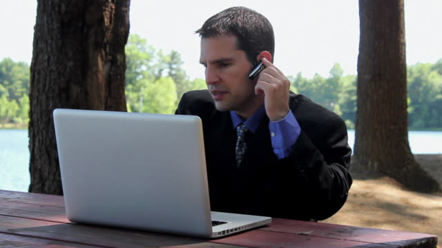ms man sitting on table and talking on bluetooth while typing on laptop near lake / portland, me, united states - one mid adult man only stock videos & royalty-free footage