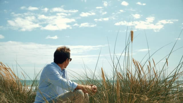 man sitting on the beach sand dunes. - contemplation stock videos & royalty-free footage