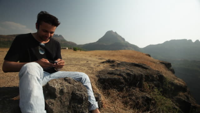 Man sitting on the cliff of mountain and talking on a mobile phone