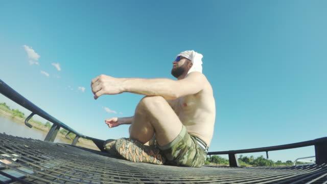 stockvideo's en b-roll-footage met man zit op het dek - in kleermakerszit