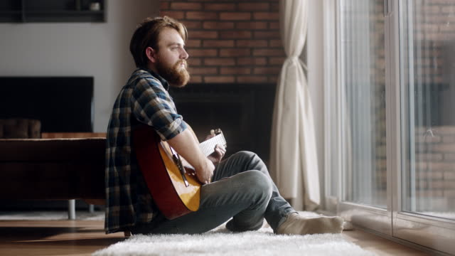 man sitting on the floor and plays guitar at home - guitar stock videos & royalty-free footage
