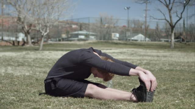 man sitting on the grass stretching. - ランニングショートパンツ点の映像素材/bロール
