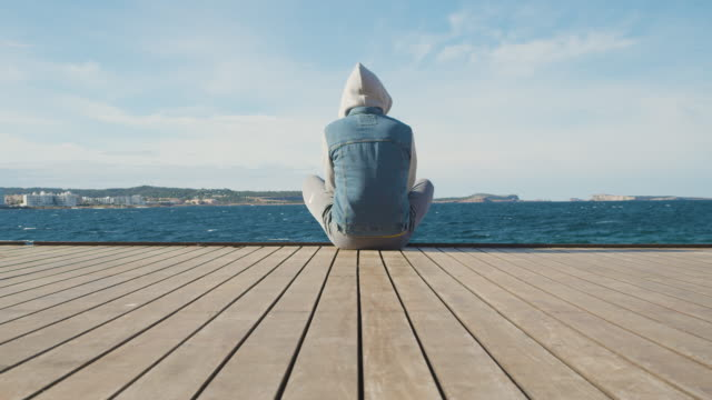 man sitting on the ground in front of the sea. 4k - adolescence stock videos & royalty-free footage