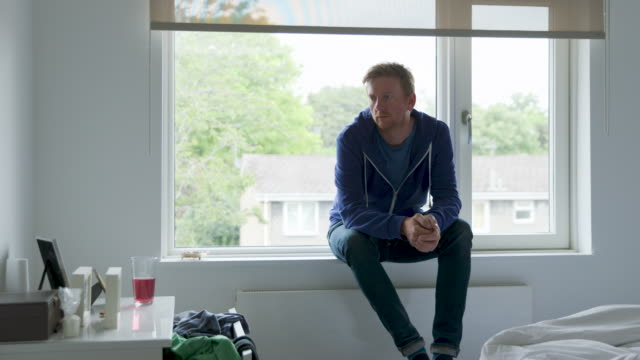 vidéos et rushes de man sitting on the window sill. he looks lost in thought - indécision