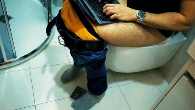トイレの上に座っている男はラップトップを使用 - 胃腸炎点の映像素材/bロール