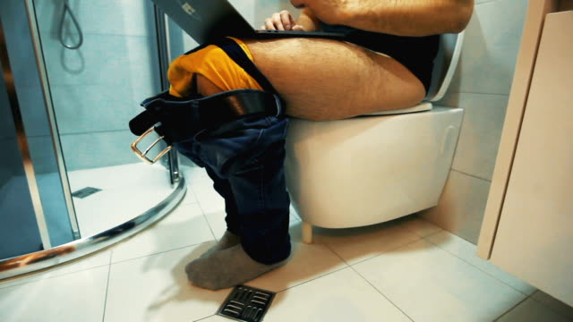 man sitting on toilet use laptop - bathroom stock videos & royalty-free footage