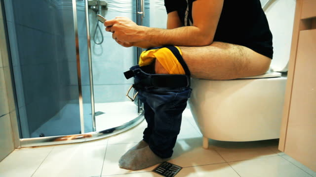 vidéos et rushes de homme s'asseyant sur la toilette emploient le téléphone intelligent - incontinence