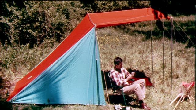 vidéos et rushes de 1958 montage ms zo ha man sitting preparing fishing rod sitting under tent flyleaf / usa / audio - camping