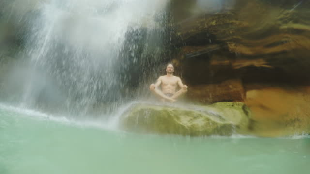 Man sitting under waterfall