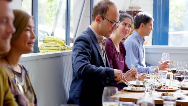 ms tu man sitting with friends at table in restaurant eating dinner - テーブルマナー点の映像素材/bロール
