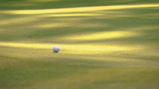 vidéos et rushes de man sizing up a shot and taking it - balle de golf