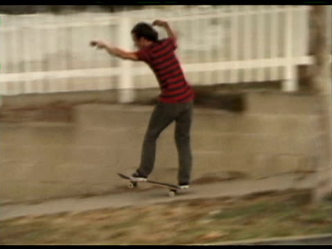 / man skateboarding down driveway into street / approaching car hits him and he narrowly avoids being run over by car / car stops to check on him and... - echtzeit stock-videos und b-roll-filmmaterial